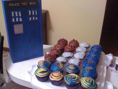 Dr. Who inspired cupcakes! In the front & right section are time travels (see next pic for cross section), on the left is chocolate/chocolate w/ red bow ties; in the center is yellow cake & cream cheese frosting with Cyberman frosting. Tardis on far left is our wine box from our wedding.