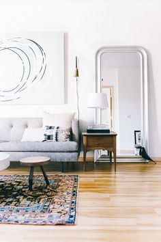 Small, bright living room with a large-scale mirror, large art, and a gray sofa