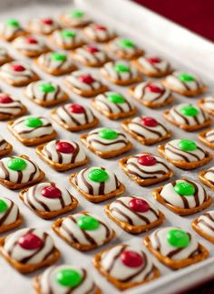 Pretzel M and M Hugs: Preheat oven to 200 degrees. Line a cookie sheet with a Silpat or parchment paper. Align pretzels on cookie sheet in a single layer then top each pretzel with one Hershey's Hug chocolate. Bake in preheated oven for 4 - 5 minutes. until the chocolate is shiny and soft (but NOT melting. the chocolates should still hold their shape). Remove from oven and carefully place one M and M in the center of each soft Hug and press down on M and M to spread the chocolate.