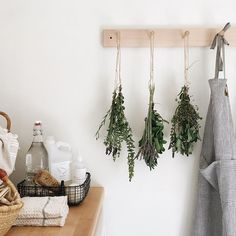 Herbs hung to dry, zero waste cleaning supplies corralled in a wire basket   Sustainable home