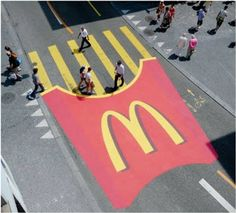Food companies are desperate to sale their product. There is a lot of competition between the different fast food brands that are out there. Therefore, all of them try to place their propagandas whenever they can. In this picture, we can appreciate how mc donalds draw their french fries in the middle of the streets to catch people's attention and persuade them to go eat at their restaurant.