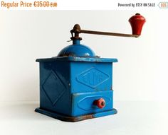 Antique Coffee Grinder, ELMA Spain, Mid Century Modern Kitchen Decor, Vintage Coffee Mill, Original Retro Style Home Decor  Perfect for collectors!  ELMA is one of the most known and best quality grinders company from Spain. They started with making coffee grinders in 1924 and since then until today ELMA grinders have been so appreciated than throughout the twentieth century most of Spanish families had one at home.  This blue tin grinder, with wooden handle and drawer pull shows its age. It…