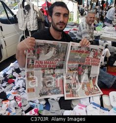 Turkish Market vendor holds up local newspaper feature on wedding of Prince William and Kate Middleton Alacatii  Turkey Stock Photo
