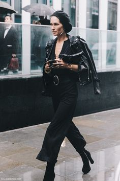 Erin Wasson wearing an all-black barrette, moto leather jacket, culottes, and ankle boots outfit.