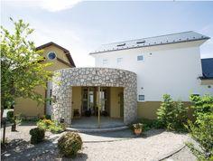 石貼りの円形ホールで蔵造りの居住棟と教会風のアトリエ棟を連結したユニークなデザイン。|モダン|砂岩|アーチ|