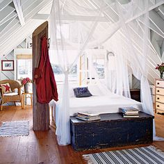 Reference Early Americana: Pine plank floors and exposed framing pay homage to early American architecture. Mosquito nets hung from overhead beams create the look of a four-poster bed while allowing the drama of the ceiling to speak for itself. Weathered wooden pieces, such as the large pine chest and tree trunk coat rack, enhance the rustic theme.