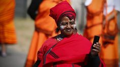 A South African woman in traditional dress takes a photograph with her mobile phone during the Mzantsi carnival parade part of Heritage day public holiday celebrations in Cape Town, South Africa on Thursday 24 September 2015