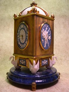 This piece was special and coveted when they stopped making it. It was made by Faberge with Wedgewood (four panels and the swans) and has pearls on each of the top corners and on the very top. It is also a key-wind swiss mechanism music box with a hidden compartment. This piece is mounted on a gorgeous blue marble base. The clock chimes on both the hour and the half hour.