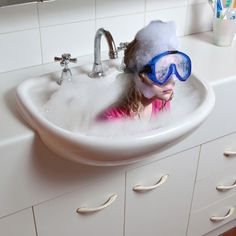 This is an awesome post modren photo. Photoshop wouldve definitly been used in this photo. Two photos would of been taken. A normal photo of the sink with bubbles in it and another with a girl with bubbles on her head, you would have to crop the girl in photoshop and then drag the cropped image and place it in the bath,that makes the illusion work