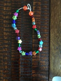 Baby girl necklace with blue green pink orange and yellow stars and some transparent beads
