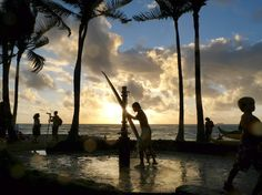 A surfer washes his board after a day on the waves at Waikiki Beach in Honolulu. [Photo by Larry Downing, Reuters]