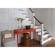 Take some classic New England styling - white painted wall panelling, wood flooring and Shaker style boxes - and then mix it up with a tangerine console table for a hallway that's always sunny