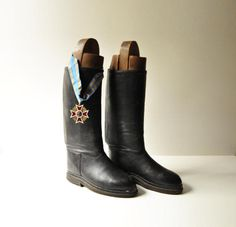 What an amazing and rare find! These fabulous black leather horse riding boots date back to WWI. They are in quite good vintage condition considering their age and use. The leather and form are very well preserved.  They come with their antique wooden shoe forms so full of character.  Their size is not marked but by wearing them I assume that they are EUR 43-44 / US 9-10 1/2.  Dimensions: height 52 cm / 20.4, sole length 22 cm / 8.6  *The medal shown in photo 1 is not incl...