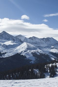 Black Snow Covered Mountain Ranges Under White Clouds and Blue Sky at Daytime