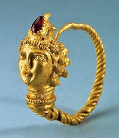 earring with the head of Dionysos; gold, with a garnet; Hellenistic, late IV/III century bc