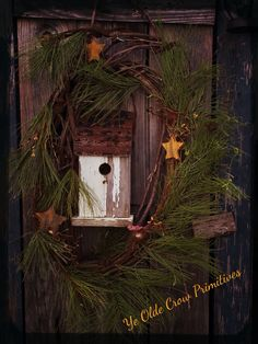 Birdhouse with some festive Christmas greens and stars on my old outhouse door. By: Ye Olde Crow Primitives