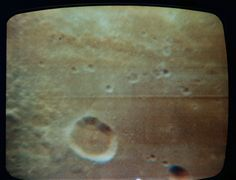 This close-up (full zoom) view of the Sea of Fertility is seen, in this color reproduction taken from the fourth television transmission, from the Apollo 11 spacecraft during its second revolution of the moon on July 19, 1969. This live TV broadcast from the moon was made by Apollo 11 astronauts Neil Armstrong, Buzz Aldrin and Michael Collins.