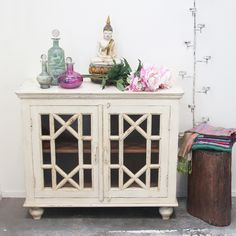 Restored Teak Glass Fronted Cabinet, coloured glassware and iron candle wall holder and silk and cashmere pashminas all from India, hand carved wooden buddha and dredged wooden stump from Northern Thailand. Support ethical and sustainable trade. Rustic Furniture, Vintage Furniture, Glass Front Cabinets, Wall Candle Holders, Northern Thailand, Indoor Outdoor Living, Interior And Exterior, Teak, Hand Carved