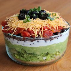 Healthy Seven-Layer Dip 2 cups chopped romaine lettuce 2 avocados, mashed well 1 cup low-fat Greek yogurt 2/3 cup black beans 1/2 cup diced tomatoes 1/2 cup shredded cheddar cheese Sliced black olives and scallions to garnish
