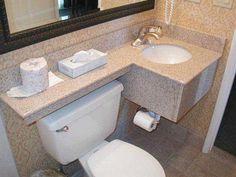 Pia de granito flutuante instalada diretamente na parede, quando escolhido este método, geralmente abaixo da pia fica um espaço vazio, você pode optar por inserir o reservatório de água do vaso, cesto de lixo ou algum objeto decorativo.
