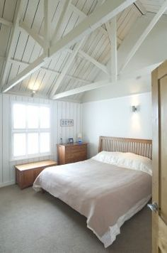 White shutters, painted timber boarding and exposed roof in this bedroom on Dartmoor, UK