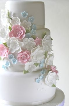 The purest white wedding cake with white, soft pink and little blue flowers. Beautiful Country Garden style.