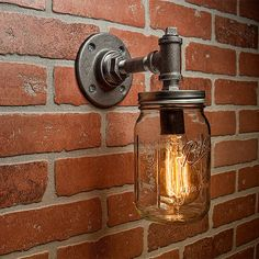A handmade industrial chic sconce that is sure to add a truly charming accent to any home. This unique and re-imagined blend of metal pipe fittings and mason jars create a unique light that will surely add a warm and welcome atmosphere to your home or business. Features a quart size Ball mason jar. This is sure to become the topic of conversation among guests, friends, family or clients.  All TMG-DZN fixtures will accept most Incandescent, CFL or LED bulbs. Light socket rated for up to 75…