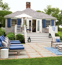 Hodgson kit cottage in Southampton with bluestone-and-brick pavers and blue patio furniture