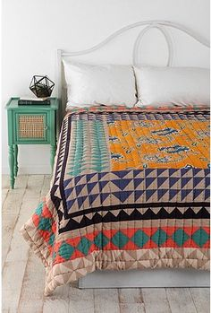 Gorgeous vintage style quilt with bright colors, aqua nightstand and white walls/bed frame.