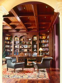 The high grid ceiling and arched entryway bring sophistication to this Tuscan-style library. The rich wooden desk complements the wall-to-wall bookshelf, while the patterned area rug brings a splash of color. Design by Debra Kay George Interiors