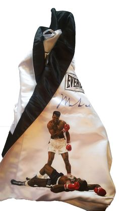 Muhammad Ali Beautiful snow white Everlast boxing robe hand-signed by the one and only Muhammad Ali in blue marker. Also painted on these trunks from the great Ken Branch is a painting of Ali over Son