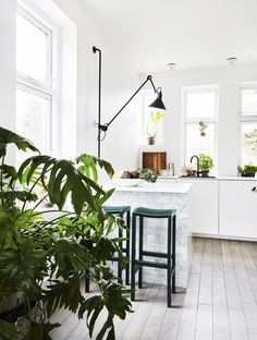 Bright and feminine kitchen, with kitchen elements all kept in white and a kitchen island with a marble effect on the sides. Small black and green details contrasts the white.