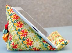 How to make a beanbag wedge stand for a tablet. I think it could be adapted for books, too.  Hey Lynn, if you could make this, I would for real buy it! :)  This would be a HUGE hit at a craft show!