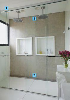 """1. Valioso principalmente em banheiros integrados ao quarto, o boxe vai até o teto e evita que o vapor se espalhe. Detalhe: é preciso haver janela ou exaustor dentro do compartimento. 2. Perfeitos para um casal, os chuveiros de teto (modelo 1997CTET, da Deca) simulam um banho de chuva. """"É o que se chama de água mole"""", explica Fábio. Repare nos dois orifícios embutidos no forro de gesso: são altofalantes do sistema de som (projeto da Home System). 3. A grelha substitui o ralo redondo com char..."""