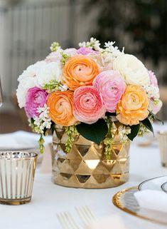 A ranunculus arrangement in pink, orange, and white in a gold vase.