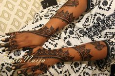 Intricate henna art on blushing bride Aisha's arms. #bellanaijabride