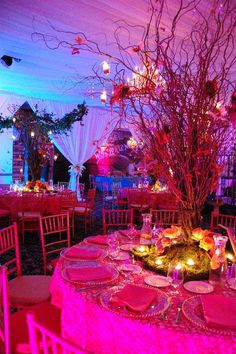 An Alice in Wonderland themed sweet 16 featured accents of colorful butterflies and hummingbirds accented the tress along with pomander balls of flowers with moss and rainbow rose accents.