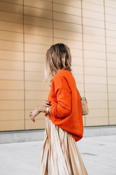 Stand out this fall with a beautiful orange cashmere sweater layered over a gold midi skirt.