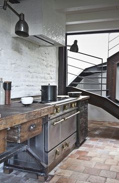 Modern rustic industrial kitchen -- whitewashed brick, terracotta tile floors, industrial wall lights