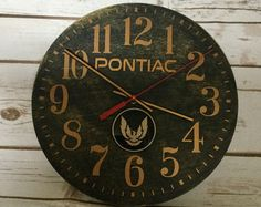 We love our classic Pontiac! It is with lots of love that this custom, one-of-a-kind Clock is designed and made! Perfect to display in your home, garage or man cave!  You will receive 1 Vintage Pontiac Firebird Emblem Clock painted Red on Birchwood and distressed for a rustic/vintage look. The back of the clock is painted White for a finished product. Measures 10 Diameter. Permanent Vinyl Decal in Black & Silver. A non sweep Quartz movement with Black hands and a Red second hand. A cherished…