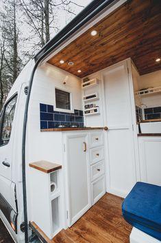 Beautiful camper van interior with wood floors, na. Beautiful camper van interior with wood floors, navy subway tile backsplash, white cabinets