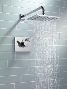 Delta Faucet Vero rain shower with cool blue subway tile make for a serene bathroom.
