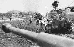 A platoon of Tiger I's and panzer-grenadiers on foot securing a Russian village.