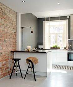 Petite cuisine ouverte sur mur en brique d'un salon