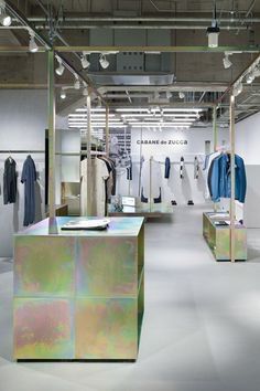 This Tokyo shop :: Schemata Architects features exposed industrial fittings and galvanized metal display rails that have been treated to produce a petrol-toned surface.