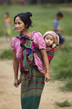 A refugee mother of three from Myanmar, walks through a refugee camp in Thailand with her youngest on her back. UNHCR's Safe Mother and Baby program is designed to improve maternal health, and reduce maternal, newborn and child morbidity and mortality. Burma Myanmar, Myanmar Women, Precious Children, Happy Baby, Mothers Love, Mother And Child, World Cultures, People Around The World, Madonna