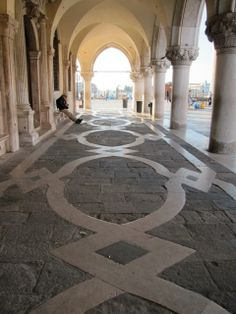 Beautiful arched passages with bold floor patterns line the perimeter of the Doge's Palace in Venice.
