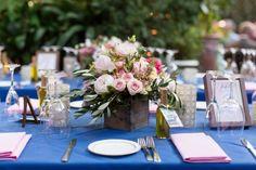 Réception de mariage en plein air avec des nappes bleues et roses pièces maîtresses florales