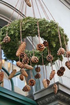 evergreen wreath with hanging pine cones - fun for an outdoor (or indoor) space (maybe string with LED battery lights?)