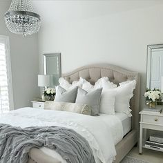 (@thedecordiet) on Instagram Tufted bed, Nicolette bed, neutral glam bedroom, bedroom inspo, white nightstands, white bedding, ruffle bedding duvet cover, antelope print pillow, chandelier over bed, mirrors over nightstand, classic gray paint by Benjamin Moore, chantilly lace paint on trim by Benjamin Moore